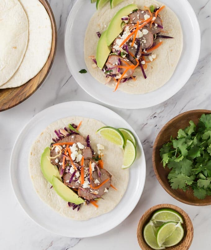 two prepared pork tacos on white plates with taco shells, coriander, and limes around