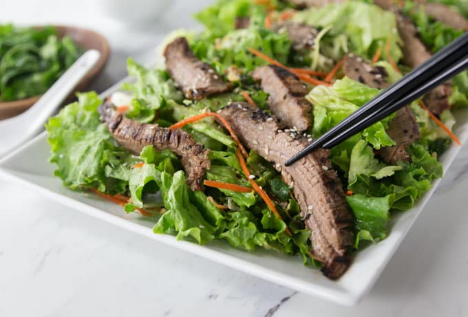 a salad on a square plate with sliced beef and chopsticks