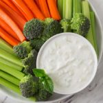 A white bowl with Greek tzatziki along with sliced carrots and celery.
