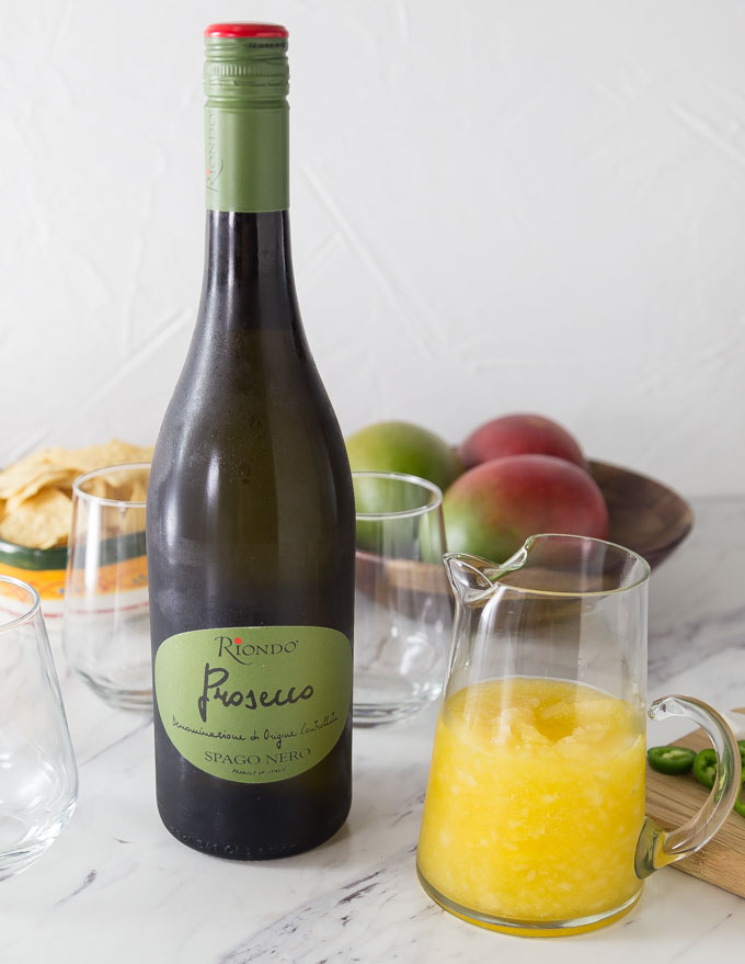 a bottle of prosecco next to a pitcher of mango cocktail with glasses and mangoes behind