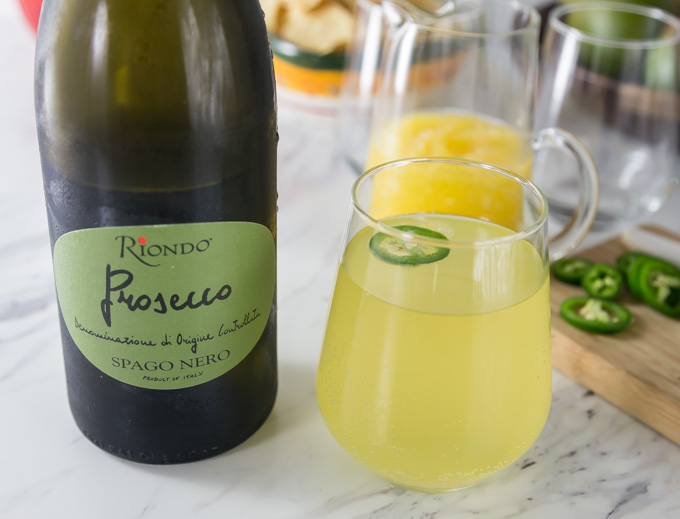 a bottle of prosecco next to a mango cocktail in a glass with a slice of jalepeno