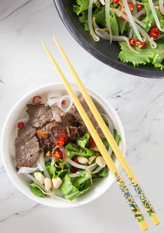 a close up of pho salad with yellow chopsticks and a serving dish above
