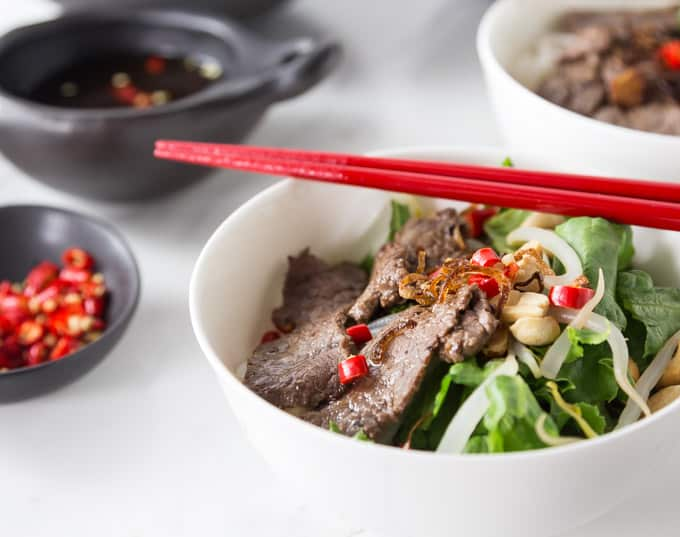 a close up of a bowl of pho tron with red chopsticks