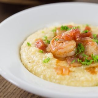 When you visit the Southern USA you have a try a bowl of this spicy dish! Some of the best comfort food comes from the American South and shrimp and grits ranks near the top! Shrimp and grits is true Lowcountry cuisine from coastal Carolina and Georgia. Imagine a spicy saucy shrimp with some creamy corn grits with cheese for a nice balance of flavor. This is a must try recipe and feel free to get creative. The grits are a blank canvas to add something spicy to. Like cajun flavors? Add some spicy cajun style shrimp. | ethnicspoon.com