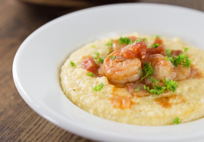 a white bowl of grits topped with shrimp and parsley