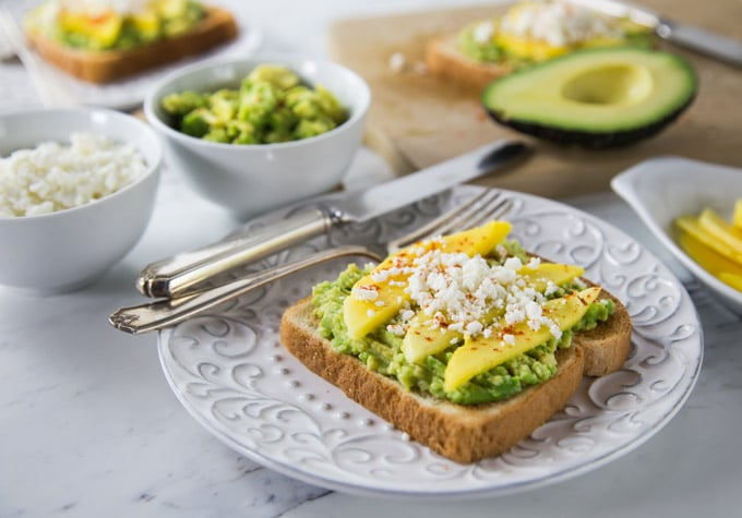 Love Latin flavors? Try a new avocado toast recipe with Latin flair! Creamy avocados with tangy mango, salty queso fresco and a sprinkle of chili powder. The combination of flavors is incredible! | ethnicspoon.com