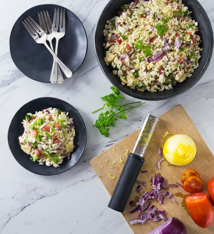 a black bowl of mediterranean orzo pasta salad with a served plate, a plate of forks, and a cutting board with ingredients