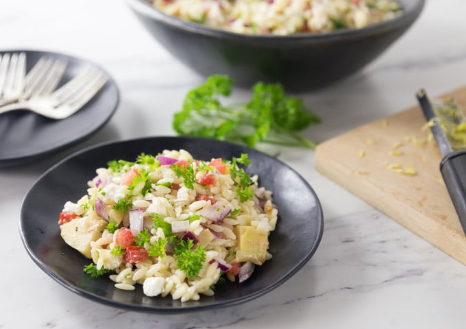 a black plate of mediterranean orzo salad with parsley on top and serving dishes in the back