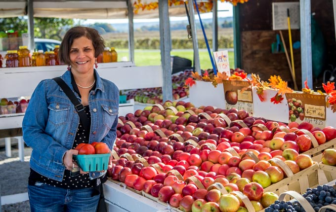 a lady buying apples at a farm stand with baskets of apples on the right