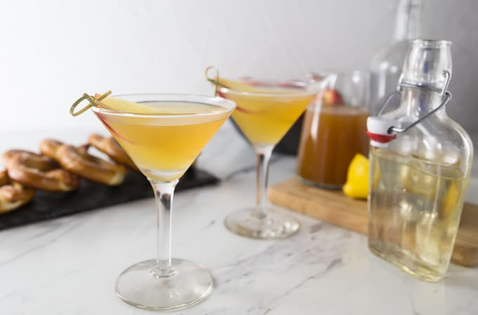 two apple cider martinis with pretzels in the back and syrup on the right