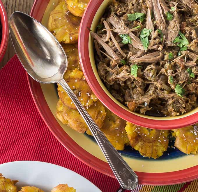 a bowl of ropa vieja with a plate of fried plantains and a spoon