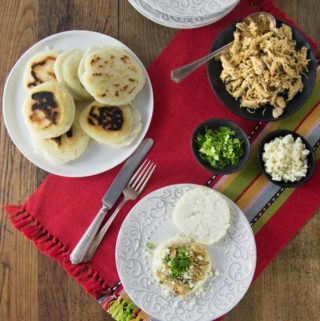 You'll love these nice warm arepas with a crunchy exterior and soft creamy middle. Arepas are a popular dish in Colombia and Venezuela. These are also gluten free made with corn flour or masarepa. I like to fill mine with some spicy shredded chicken and queso fresco. Here is an easy recipe to make arepas at home and the dough comes together quickly and you can brown them on a cast iron skillet or griddle. | ethnicspoon.com