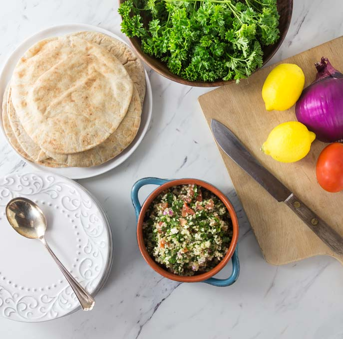 a bowl of tabbouleh, a cutting board with lemons, a bowl of parsley, and a plate of pita on a marble countertop