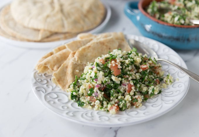 a white plate with tabouleh and pita
