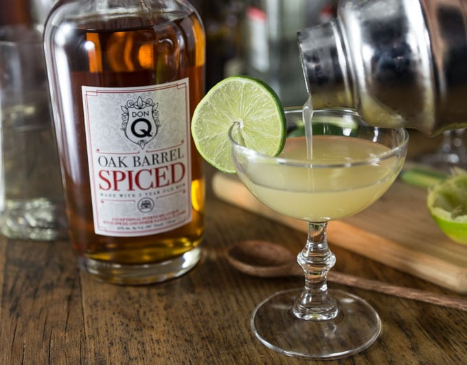 a bottle of don q spiced rum and a shaker pouring into a glass with a wedge of lime