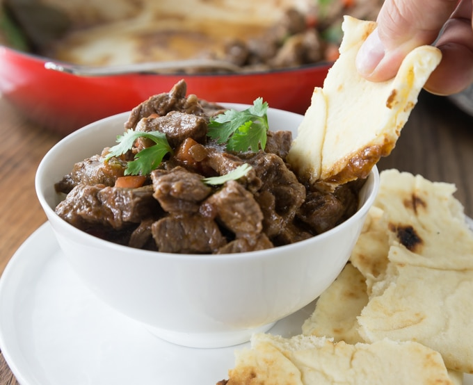 a bowl of lamb stew with naan dipping in and naan on the saucer