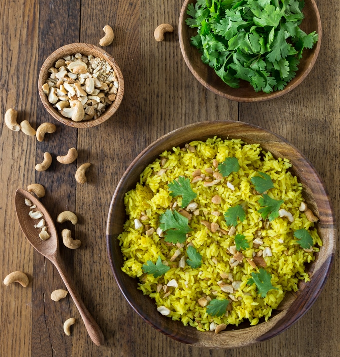 bowls of crushed cashews, cilantro, a wooden spoon and yellow rice