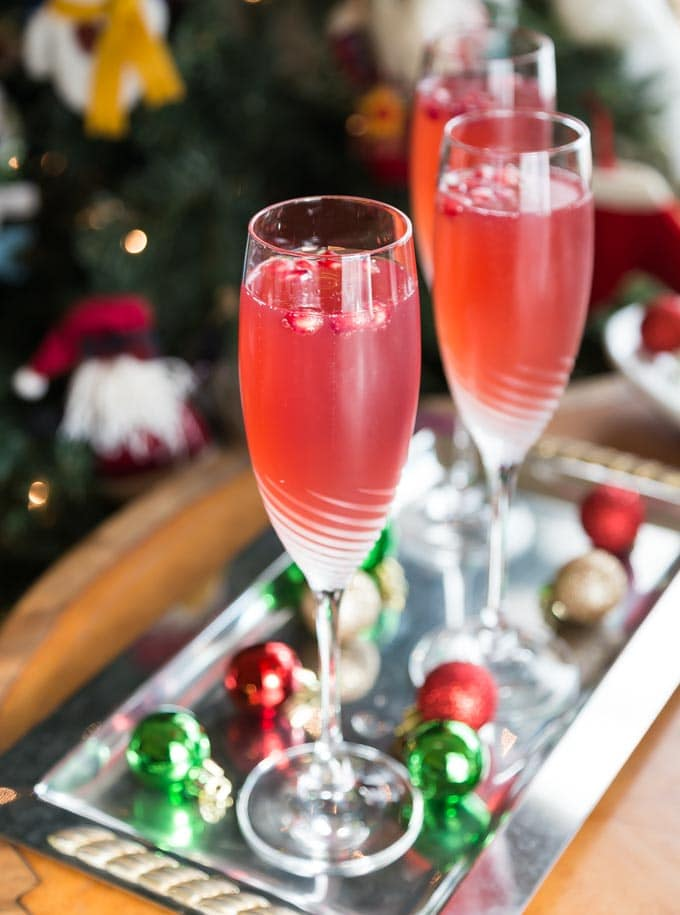 three pomegranate mimosas on a tray with christmas bobbles
