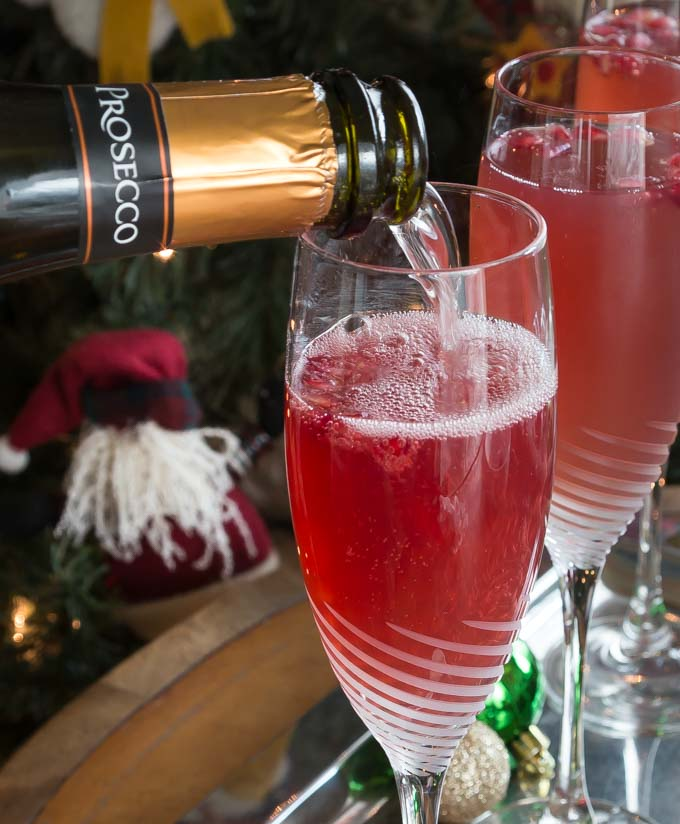 prosecco pouring into a champagne glass with red liquid and christmas stuff in the background