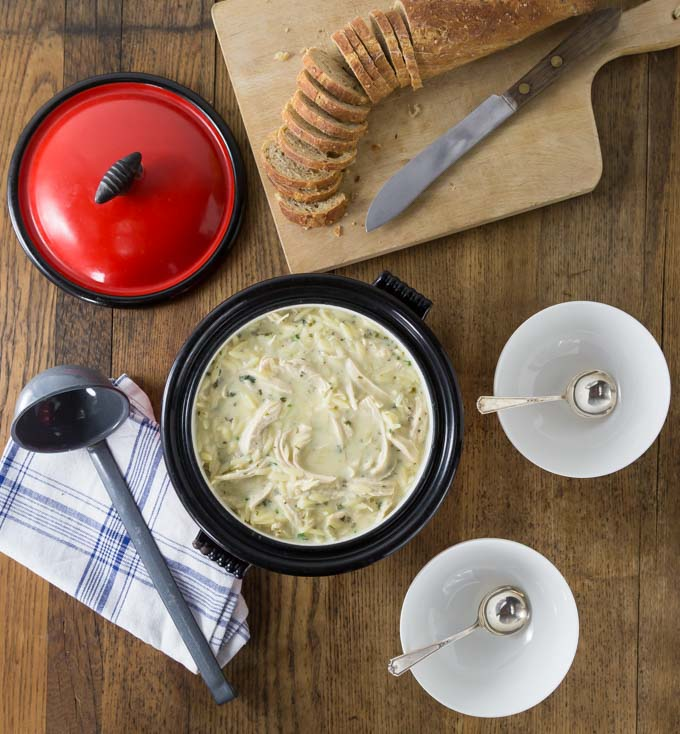 a dutch oven filled with chicken soup and sliced bread and two spoons in bowls on the right