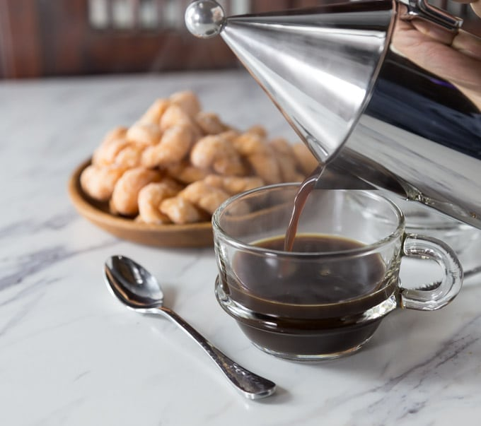 a glass mug of coffee being poured with a spoon on the left