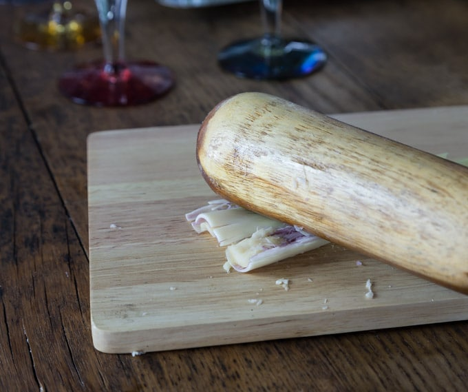a stalk of lemongrass getting smashed on a cutting board