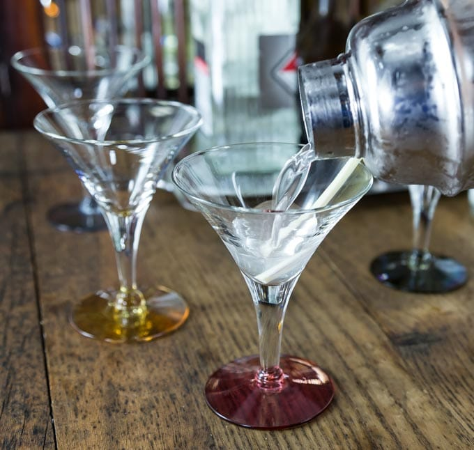 a shaker pouring lemongrass martini into a glass on bar
