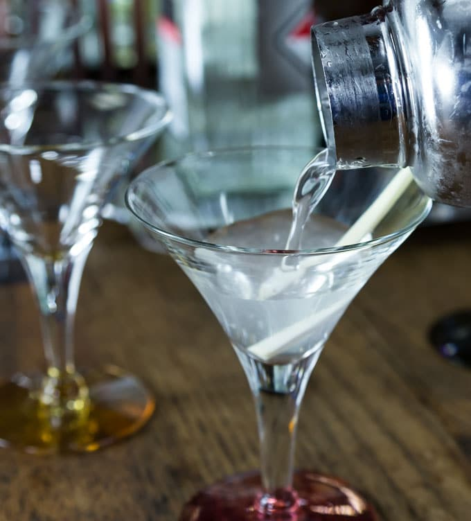 a shaker pouring lemongrass vodka martini into a glass