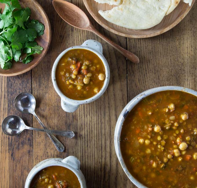 a pot of moroccan lentil soup, two bowls of soup, a plate of cilantro and a plate of naan