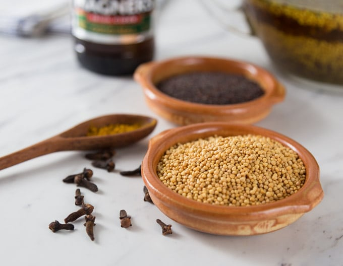 two bowls of mustard seed and ground cloves with a wooden spoon on the left