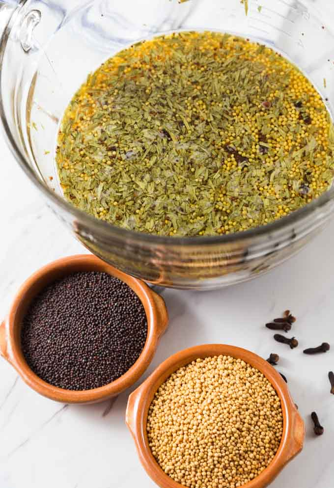 a bowl of water with mustard spiced soaking and two bowls of mustard seeds on the bottom