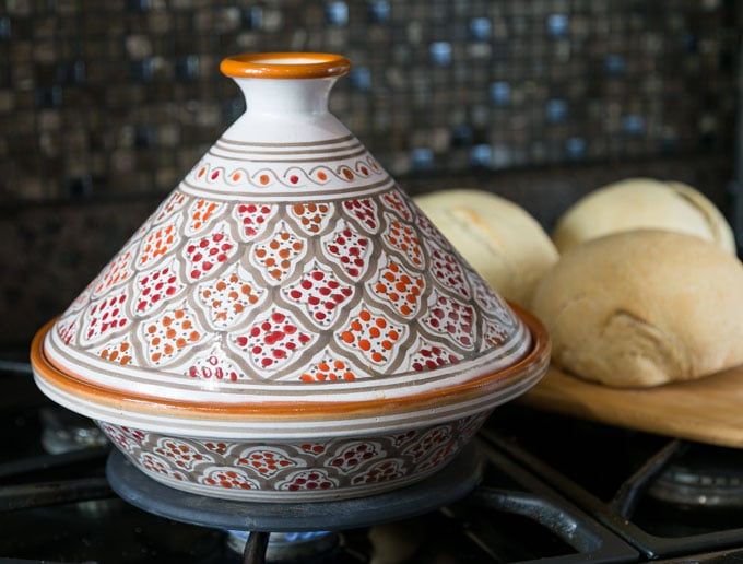 an orange tagine on the stove with bread in the back