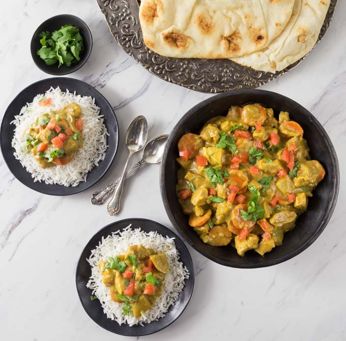 a big bowl of chicken curry and two smaller bowls of curry with rice on the left, a plate of naan in the top center