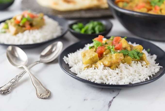 Here is a must try chicken dish with a spicy creamy coconut almond curry sauce. This has just a light amount of heat in a rich nutty and silky sauce. Serve this over some basmati rice and top with fresh diced tomato and cilantro. | ethnicspoon.com