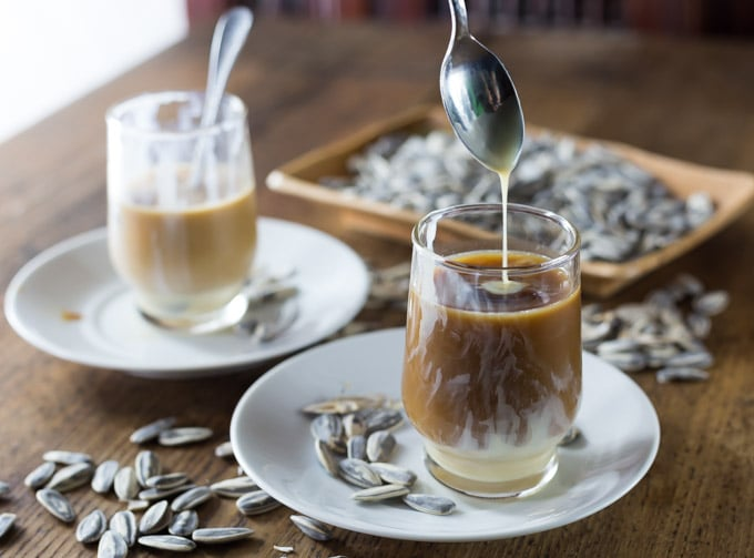 a spoon adding condensed milk to a glass of coffee