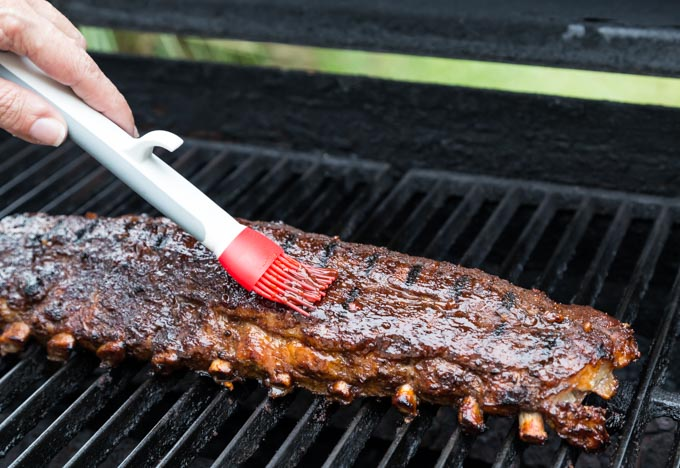 a rack of ribs on a grill with a brush spreading sauce