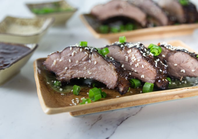 three bbq ribs on a plate with sesame seeds and green onions