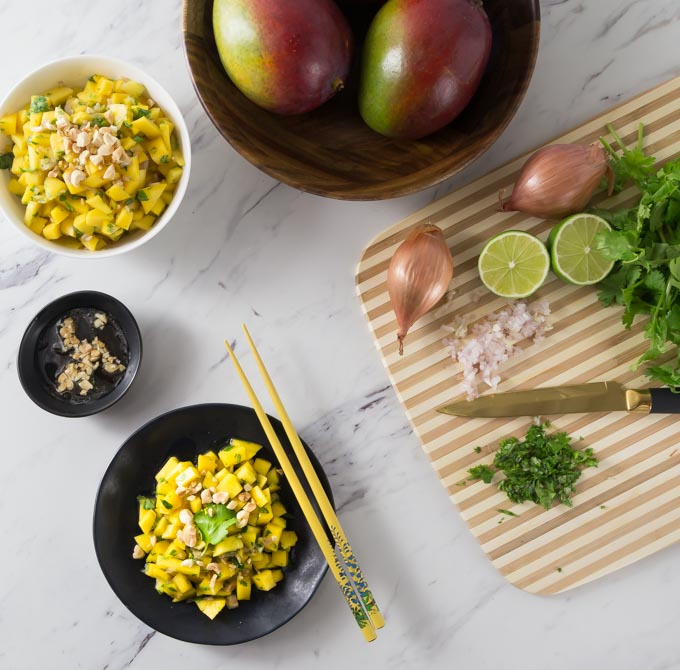 a bowl of vietnamese mango salad with chopsticks surrounded by chopped ingredients on a cutting board