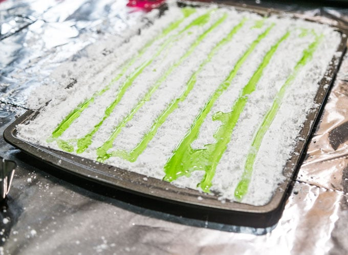 Flavored hard candy poured into powdered sugar troughs on a baking sheet.