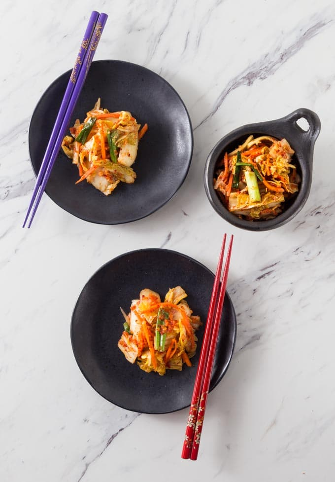 Two plates of kimchi on black plates with chop sticks and a black serving bowl.