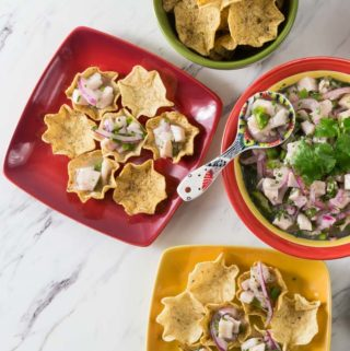 A red serving plate with a large bowl of tilapia ceviche.