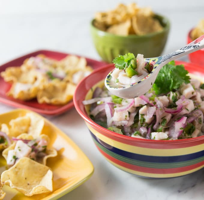 A photo of tilapia ceviche in a stripped bowl with chips and serving plates.