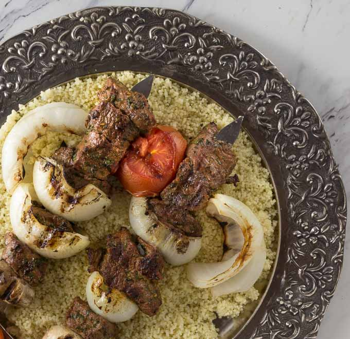 Beef kebab on a silver platter with couscous.