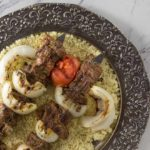 Moroccan style grilled beef kebab with tomato, onion and couscous.