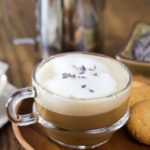 A photo of a clear glass coffee cup with lavender latte sprinkles with dried lavender.
