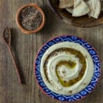 A bowl with hummus and za'atar with a wooden spoon.