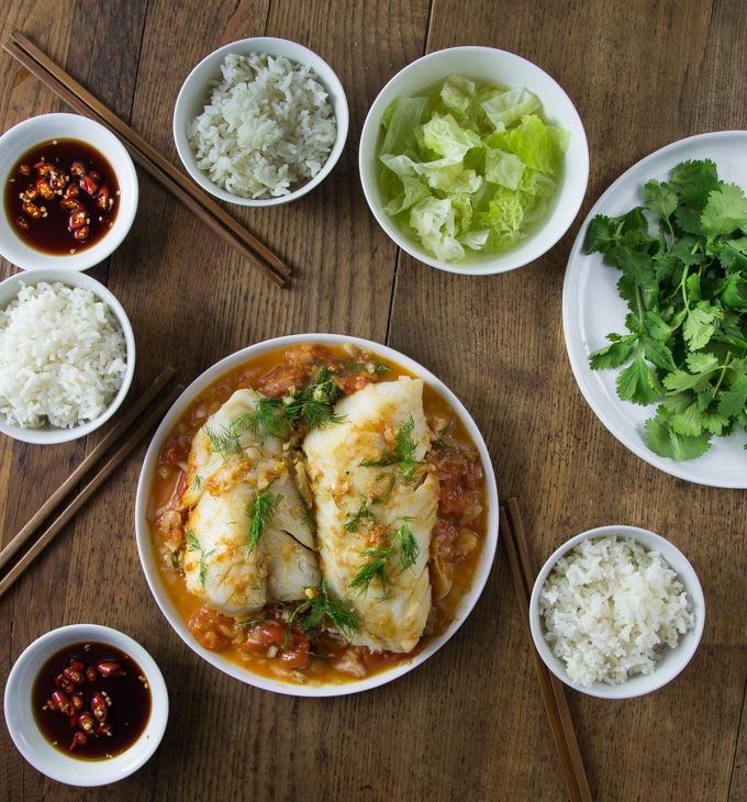 A large plate with Vietnamese tomato fish, a dish of soy sauce and rice bowls.