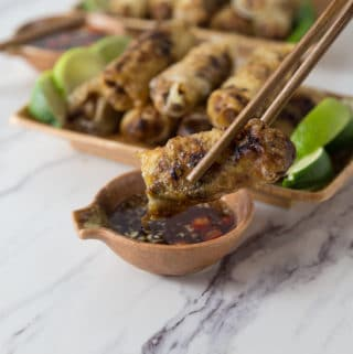 A photo of a Vietnamese spring rolls being dipped into sauce with chopsticks.