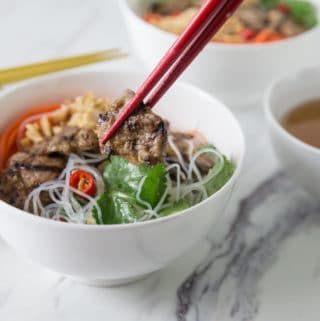 Red chopsticks lifting a piece of grilled pork from a white bowl with noodles.
