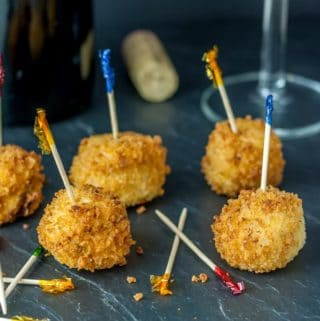 A photo of croquetas with toothpicks on a black plate.